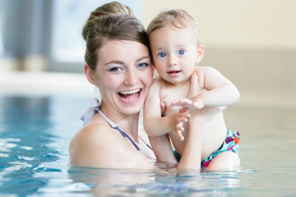 Mutter mit neugeborenem Kind beim Babyschwimmen