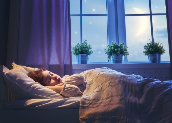 Maedchen schlaeft in ihrem Bett