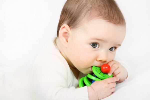 Baby spielt mit einem Holzspielzeug