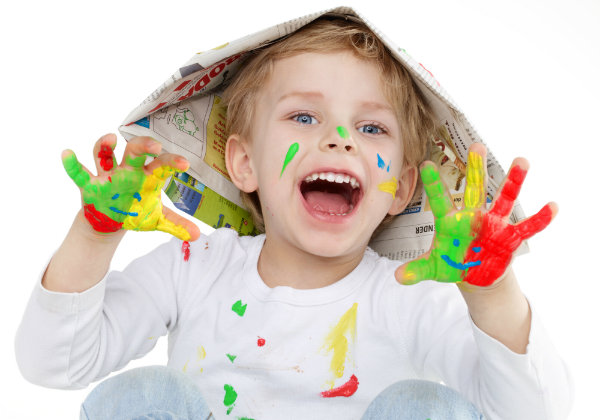 Kleiner Junge mit bemalten Haenden durch Fingerfarbe