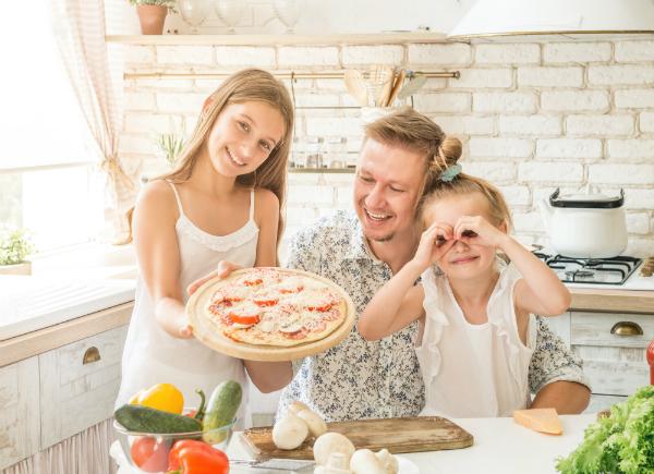 Vater bereitet mit seinen Toechtern eine Pizza vor