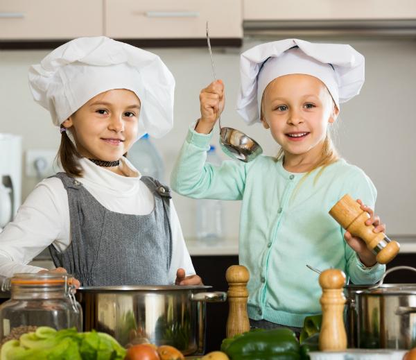 Zwei Maedchen bereiten Gemuese vor