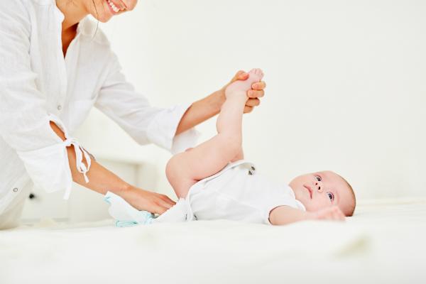 Fuersorgliche Mutter wechselt Baby Windeln