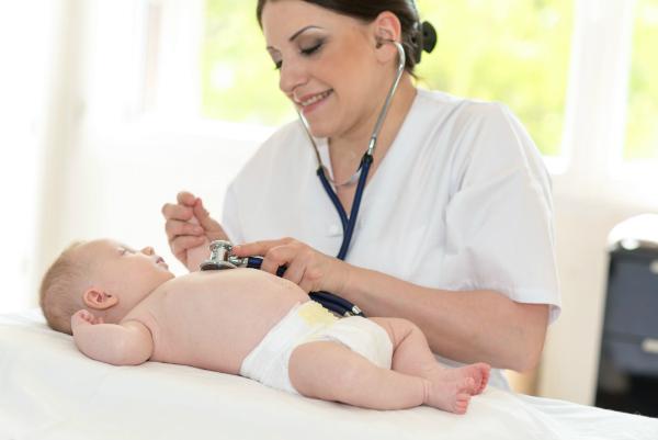 Kinderaerztin untersucht Baby