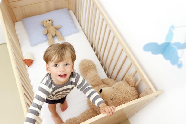Zweijaehriger Junge steht in seinem Kinderbett mit Plueschtieren