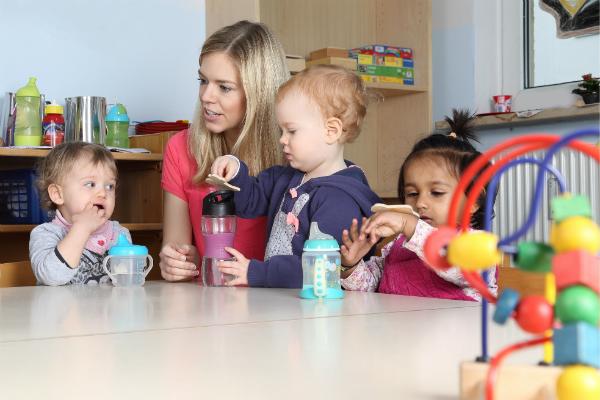 Erzieherin mit Kindern am Tisch