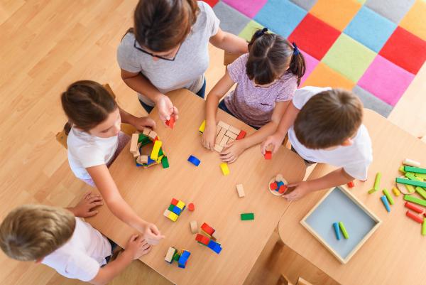 Erzieherin spielt mit Kindern und Baukloetzen