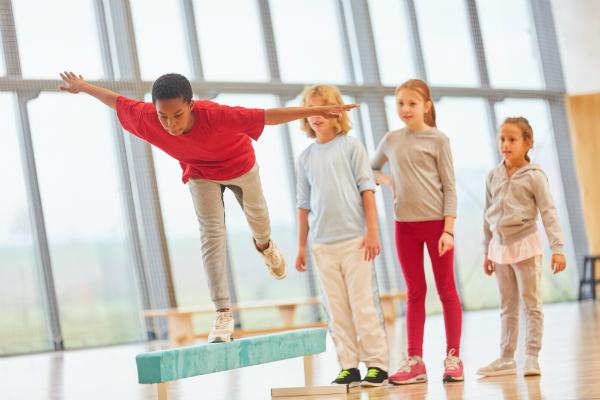 Kinder balancieren auf einem Schwebebalken