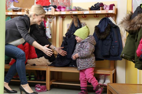 Mutter holt freudig ihr Kind von Kinderkrippe ab