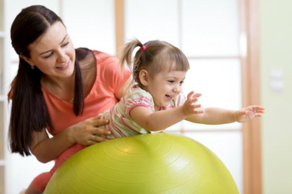 Mutter und Kind spielen mit Gymnastikball