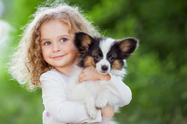 Kleines Maedchen mit Welpe im Arm