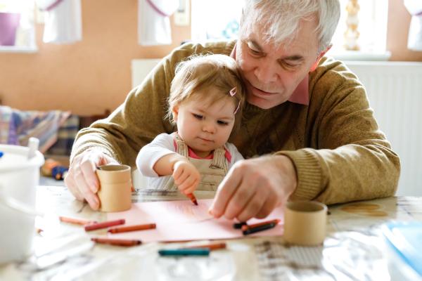 Kleines Maedchen und Grossvater malen mit Wachsmalstiften