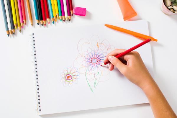 Maedchen zeichnet bunte Blume