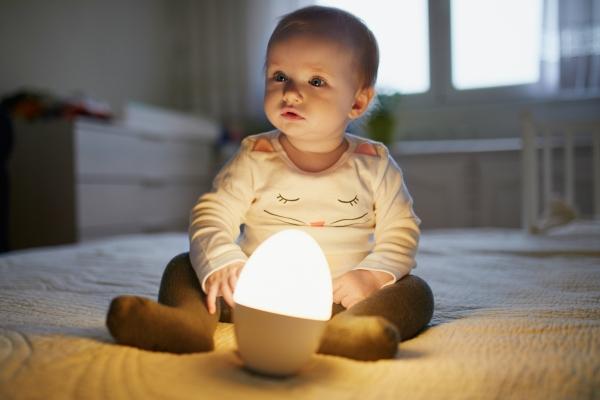Baby spielt mit Nachttischlampe