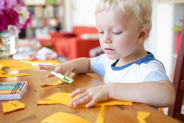 Junge bastelt mit Schere und Papier
