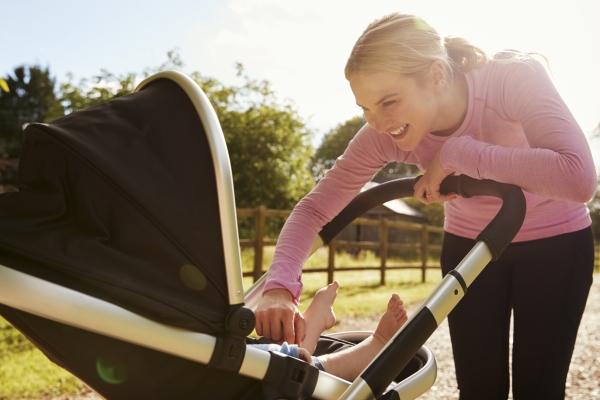 Spazieren mit dem Kinderwagen im Sonnenschein