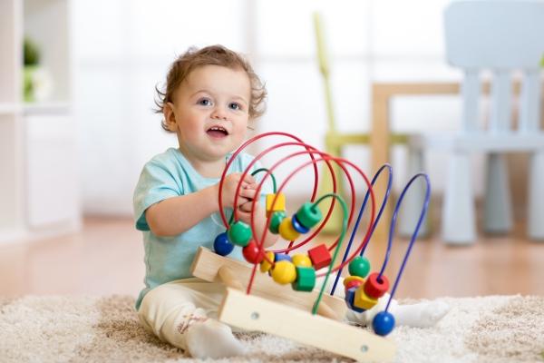 Baby spielt mit paedagogischem Spielzeug