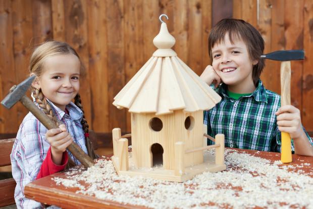 Zwei Kinder bauen ein Vogelhaus