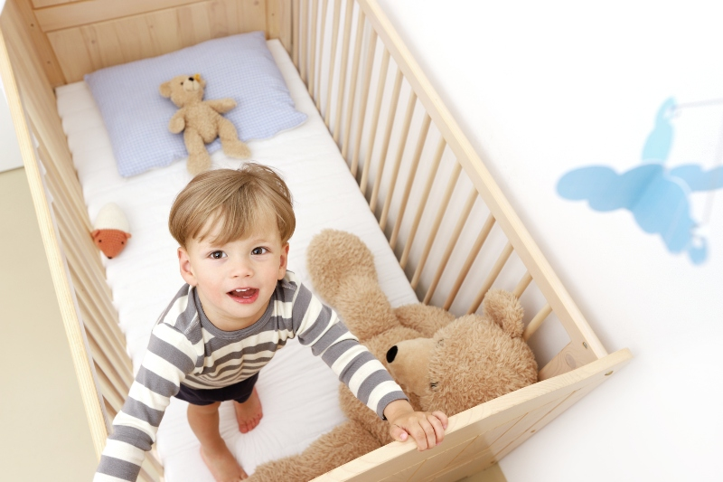 Ein zweijaehriger Junge steht in seinem Kinderbett