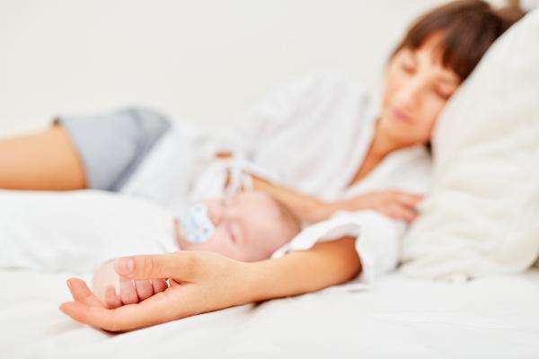 Mutter und neugeborenes Baby halten friedlich Mittagsschlaf Hand in Hand