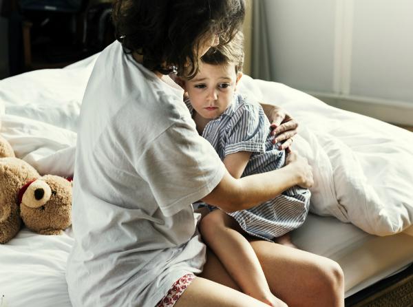 Mutter troestet kleinen Jungen nach Albtraum