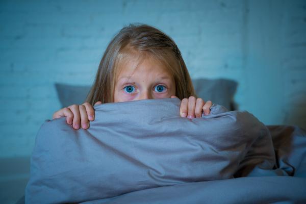 Schlafloses Maedchen versteckt sich hinter der Decke