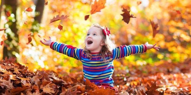 Kind spielt in herbtslichem Laub