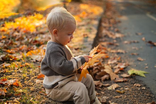 Kind spielt mit großem Laubblatt