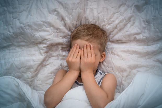 Kind hält sich aus Angst die Hände vor das Gesicht