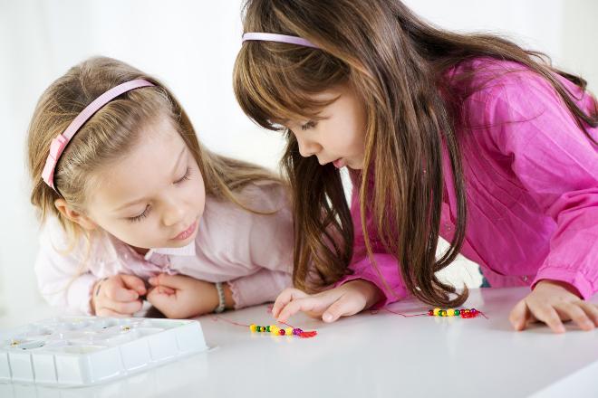 2 Kinder basteln mit Perlen