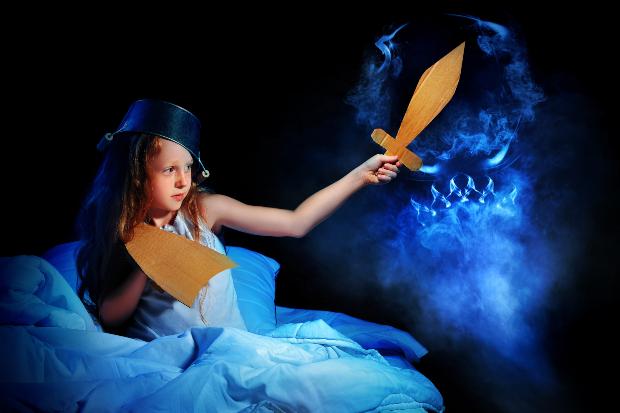 Mädchen im Bett kämpft in der Nacht gegen Monster